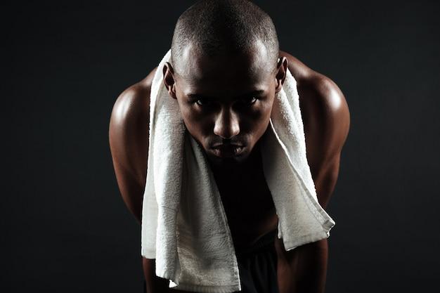 Cansado homem afro-americano de esportes com uma toalha nos ombros, relaxante após treino Foto gratuita