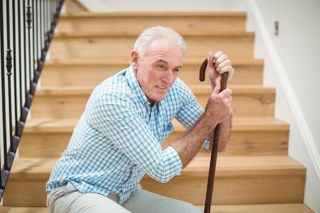 Cansado homem idoso sentado na escada Foto Premium