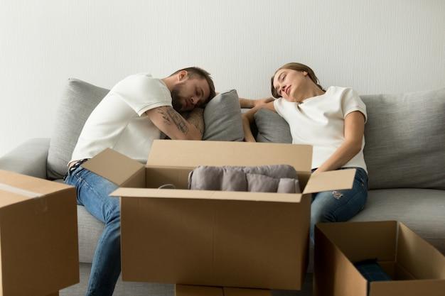 Cansado jovem casal relaxando no sofá se movendo para casa nova Foto gratuita
