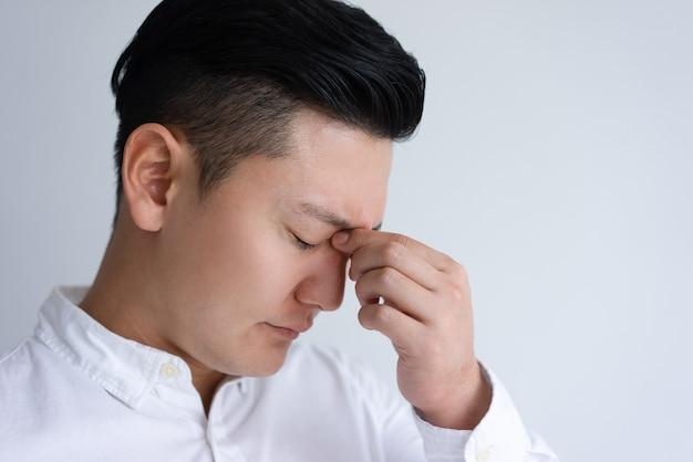 Cansado jovem homem asiático tocando sua ponte do nariz Foto gratuita