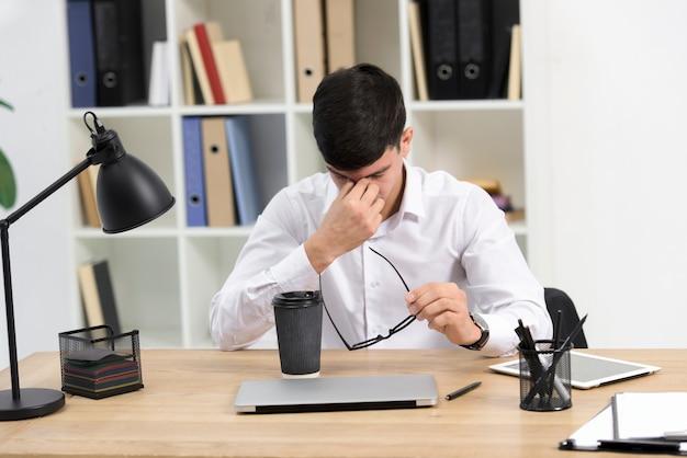 Cansado, jovem, homem negócios, segurando, óculos, em, mão, com, takeaway, xícara café, e, laptop, escrivaninha Foto gratuita