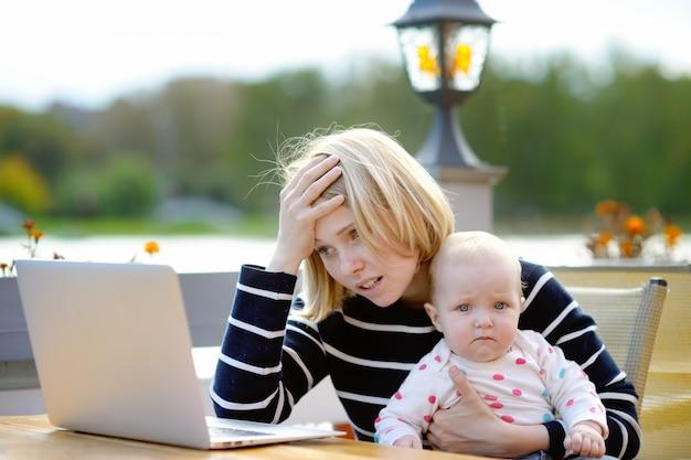 Cansado jovem mãe trabalhando oh seu laptop e segurando a filha de 6 meses Foto Premium