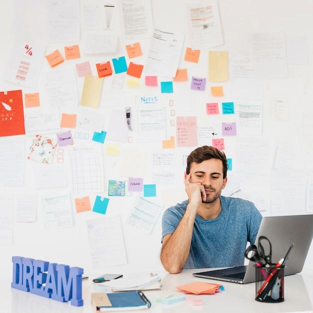 Cansado jovem sentado perto de laptop contra a parede com notas Foto gratuita