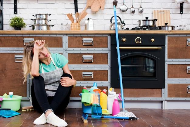Cansado mulher sentada no chão da cozinha com produtos e equipamentos de limpeza Foto gratuita