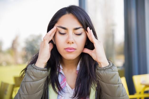 Cansado mulher tocando templos ao ar livre Foto gratuita