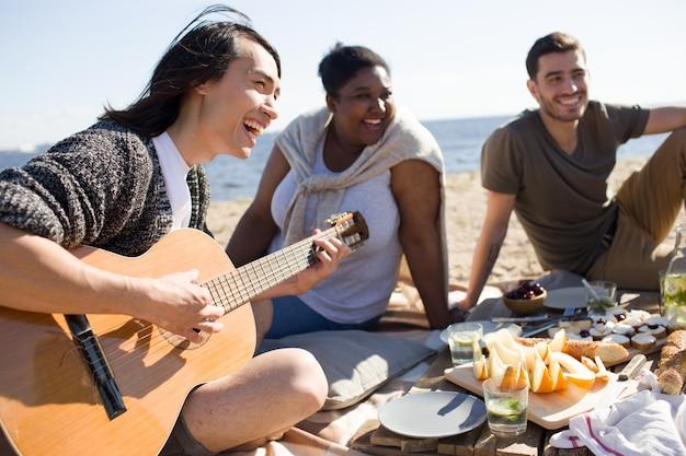 Cantando e tocando guitarra em um piquenique Foto gratuita