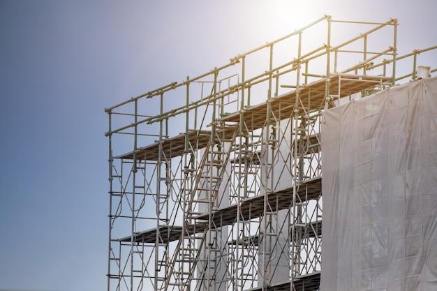 Canteiro de obras com torre de andaime e etiqueta de aviso de construção com céu, andaimes para fábrica de construção Foto Premium