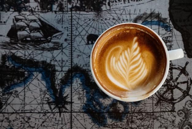 Canto de lattee no fundo do mapa do mundo e conceito do copyspace, da bebida e da bebida. Foto Premium