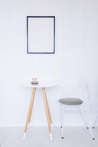 Canto de uma cozinha com mesa, cadeiras cinza e um cartaz pendurado em uma parede cinza clara. Foto gratuita
