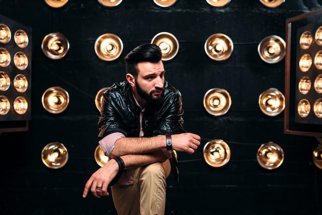 Cantor barbudo em jaqueta de couro preta no palco com enfeites de luzes Foto Premium