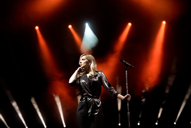 Cantor em cena no clube. iluminação de palco brilhante. Foto Premium