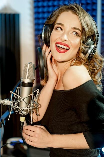 Cantora atraente com fones de ouvido na frente do microfone canta com a boca aberta e com uma expressão de felicidade no rosto. jovem mulher cantando no estúdio de gravação. Foto Premium