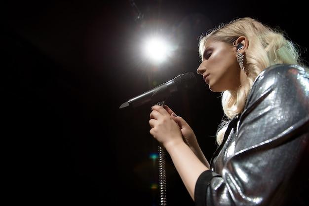 Cantora e microfone. mulher de cantor no palco. Foto Premium