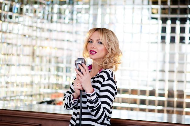 Cantora em um vestido longo perto do microfone. Foto Premium