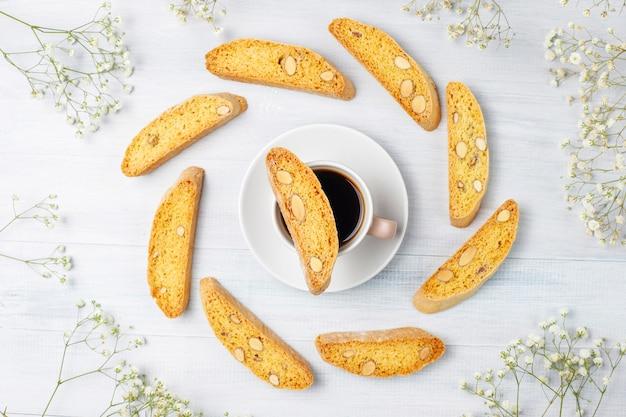 Cantuccini de biscoitos tradicionais da toscana italiana com amêndoas, uma xícara de café na luz Foto gratuita