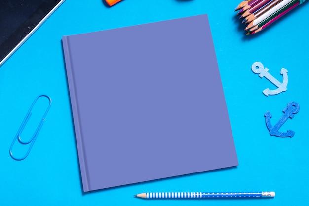 Capa de livro vazio azul simulado acima, em cima da mesa com estacionário Foto Premium