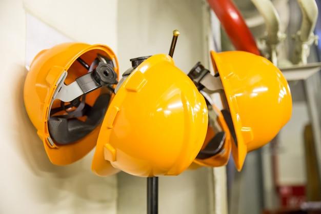 Capacete amarelo do desgaste de segurança do capacete pendurado no cabide no canteiro de obras Foto Premium