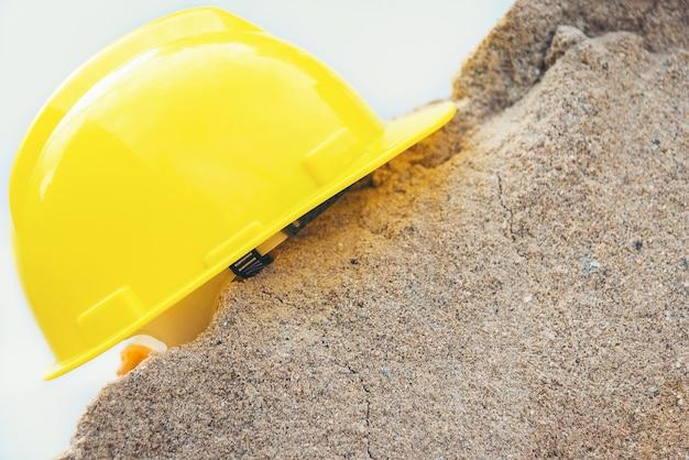 Capacete amarelo e casa modelo de madeira em uma pilha de areia Foto Premium