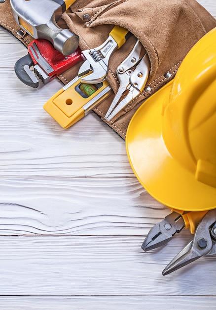 Capacete de cinto de construção de couro no conceito de manutenção de tábua de madeira Foto Premium
