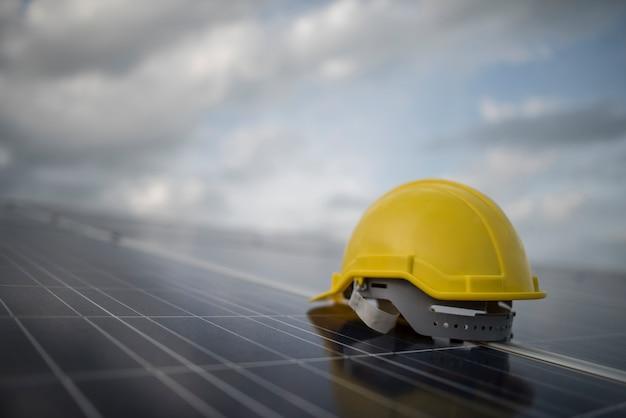 Capacete de segurança amarelo no painel da célula solar Foto gratuita