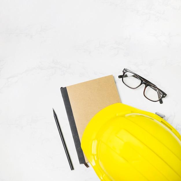 Capacete de segurança e óculos perto de diário de construção Foto gratuita