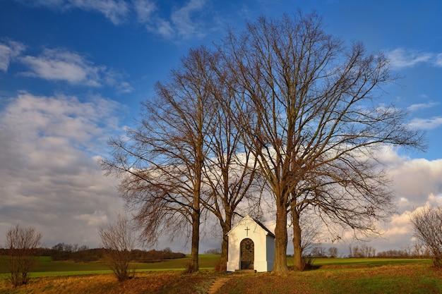 Capela pequena bonita com paisagem e árvores no por do sol. nebovidy - república checa. Foto gratuita