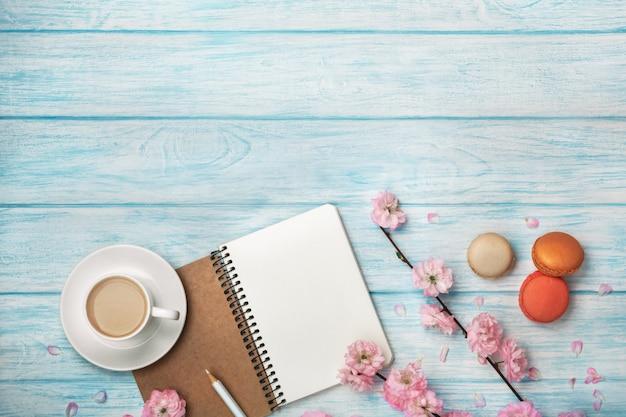 Cappuccino branco do copo com flores de sakura, caderno, macarons, em uma tabela de madeira azul Foto Premium