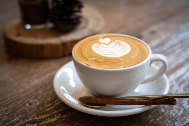 Cappuccino com arte do latte no fundo de madeira. espuma bonita Foto Premium