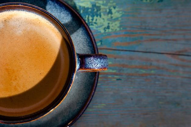 Cappuccino com espuma, xícara de café azul sobre fundo de madeira Foto Premium