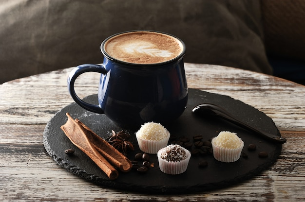 Cappuccino em uma caneca, canela e cupcakes com creme e chocolate Foto Premium