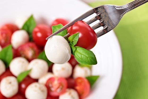 Caprese salada no garfo Foto gratuita