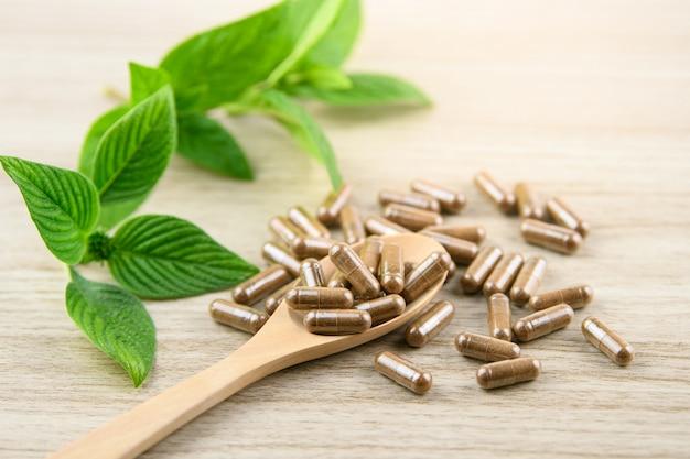 Cápsula de ervas da natureza ervas para uma boa saúde, suplemento de comprimidos na mesa de madeira Foto Premium