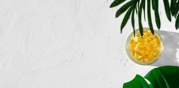 Cápsulas de óleo de peixe com ômega 3 e vitamina d em um frasco de vidro sobre uma superfície de concreto branco Foto gratuita