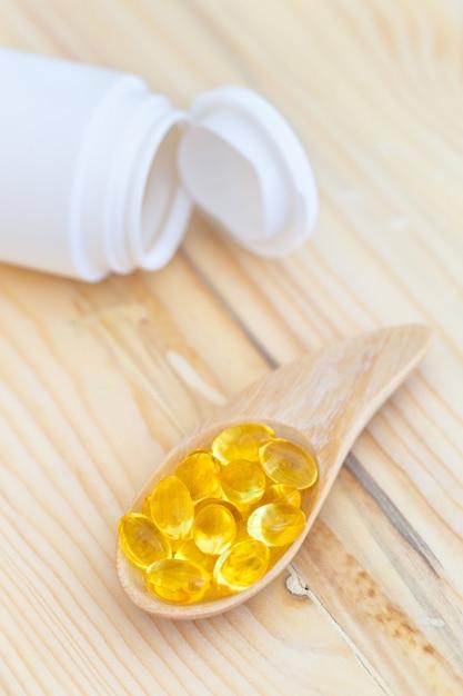 Cápsulas de óleo de peixe com ômega 3 e vitamina d na madeira colher com uma garrafa na textura de madeira Foto Premium