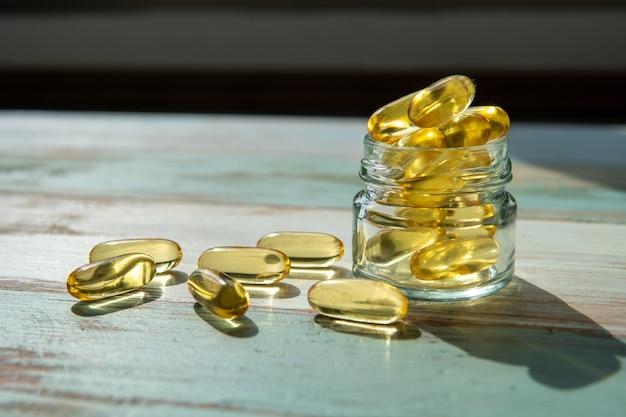 Cápsulas de óleo de peixe num frasco de vidro na mesa de madeira, conceito de saúde Foto Premium