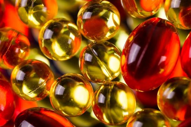 Cápsulas médicas amarelas e vermelhas em uma superfície do espelho Foto Premium