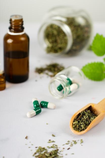Cápsulas médicas de close-up com ervas em cima da mesa Foto gratuita