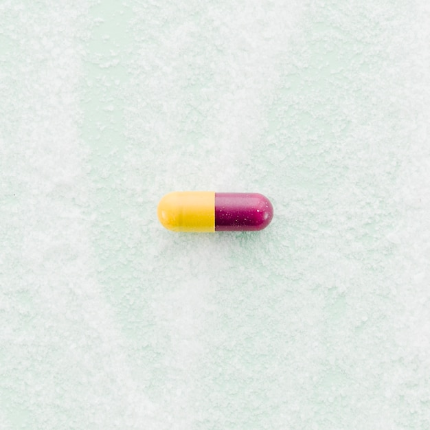 Cápsulas vermelhas e amarelas no pano de fundo texturizado Foto gratuita