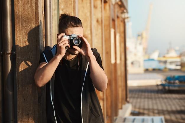 Capturando todos os momentos da vida. foto ao ar livre do jovem fotógrafo elegante olhando através da câmera vintage, tirando fotos do porto, iates e beira-mar, trabalhando como operador de câmera freelancer Foto gratuita