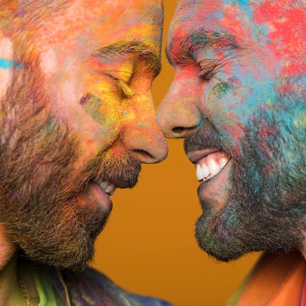 Cara a cara casal de homens homossexuais felizes em tinta colorida Foto gratuita