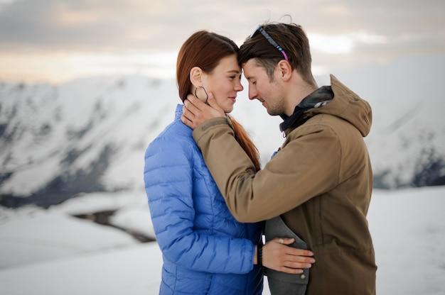 Cara abraça uma garota contra uma cena de montanhas cobertas de neve cinza Foto Premium