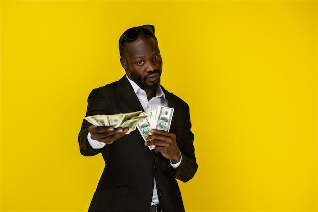 Cara afro-americana está segurando muito dinheiro com as duas mãos e olha na frente dele Foto gratuita