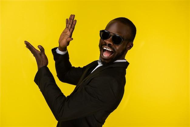 Cara afro-americana jovem de luxo barbudo está batendo palmas de mãos em óculos escuros e terno preto Foto gratuita