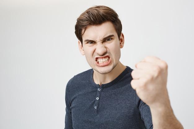 Cara agressivo com raiva fazendo careta e balançando o punho Foto gratuita