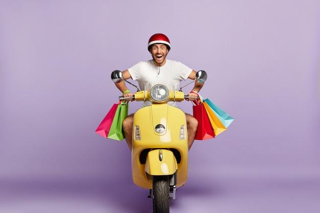 Cara alegre com capacete e sacolas de compras, dirigindo uma scooter amarela Foto gratuita