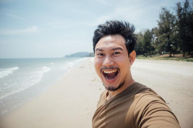 Cara alegre e feliz do selfie do homem ele mesmo na praia. Foto Premium