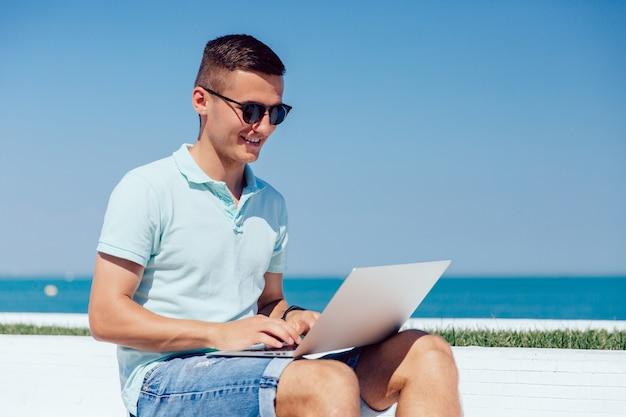 Cara alegre em óculos de sol, trabalhando no laptop, digitando, navegando sites Foto gratuita