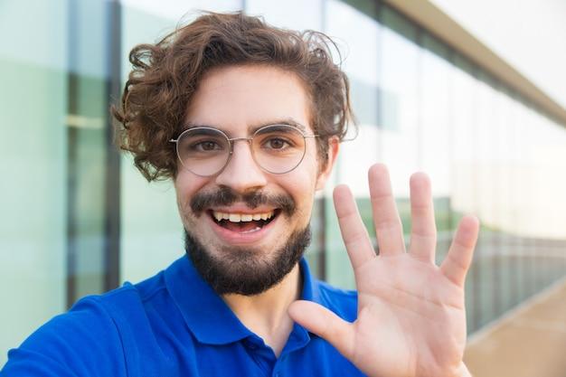 Cara alegre feliz usando óculos, acenando olá Foto gratuita