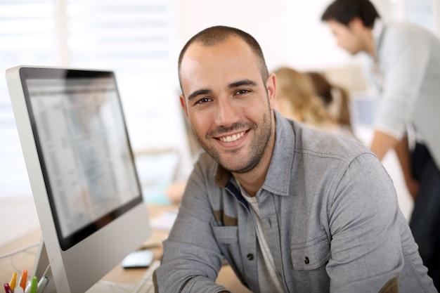 Cara alegre sentado em frente ao computador desktop Foto Premium