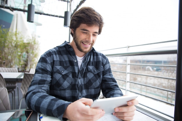 Cara alegre, usando o gadget para conversar Foto gratuita